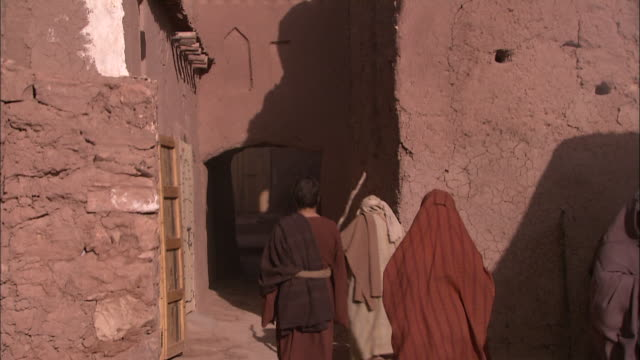 robed people walking into a narrow alley. - historical reenactment stock videos & royalty-free footage