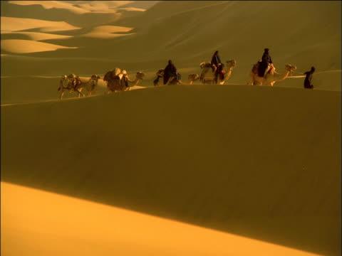Robed travellers ride and lead camel caravan up ridge of golden desert dunes