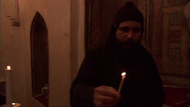 a robed worshipper lights candles in a church. - worshipper stock videos & royalty-free footage