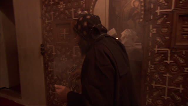 a robed worshipper spreads smoke from an incense holder near a church altar. - worshipper stock videos and b-roll footage