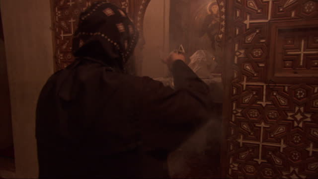 a robed worshipper spreads smoke from an incense holder near a church altar and then bows to pray. - worshipper stock videos and b-roll footage