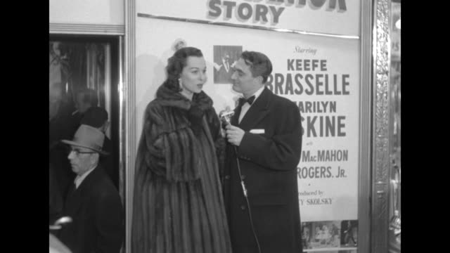 Robert Alda interviews Bess Myerson wearing fur coat outside the Paramount Theater at the premiere of The Eddie Cantor Story