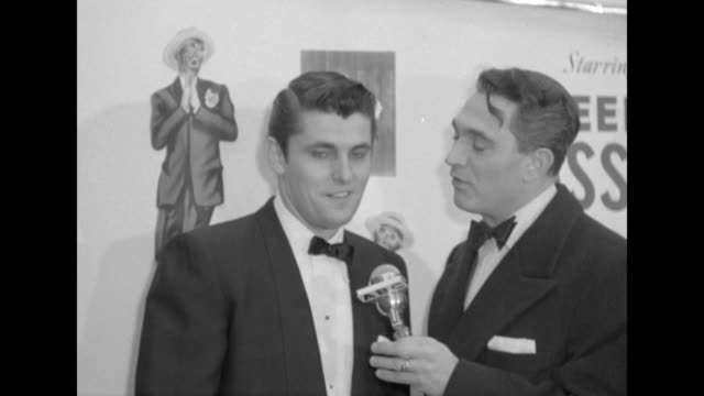 Robert Alda interviews lead actor Keefe Brasselle outside the Paramount Theater at the NYC premiere of The Eddie Cantor Story