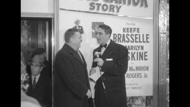 Robert Alda interviews Sam Levenson outside the Paramount Theater at the premiere of The Eddie Cantor Story