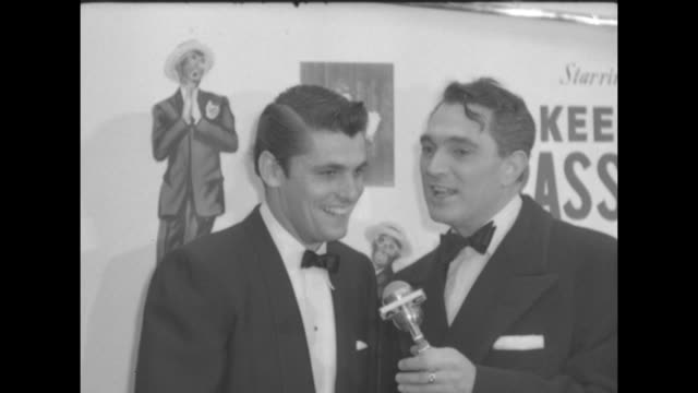 VS Robert Alda interviews the star of the movie Keefe Brasselle see blackface images of him in poster for the movie on the wall behind them / behind...