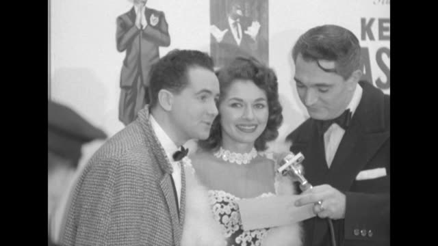 Robert Alda interviews unidentified celebrity couple outside the Paramount Theater at the premiere of The Eddie Cantor Story