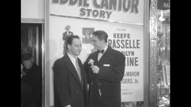 Robert Alda interviews unidentified male celebrity outside the Paramount Theater at the premiere of The Eddie Cantor Story Possibly Georgie Price