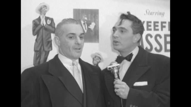 robert alda interviews unidentified male celebrity outside the paramount theater at the premiere of the eddie cantor story. - filmpremiere stock-videos und b-roll-filmmaterial