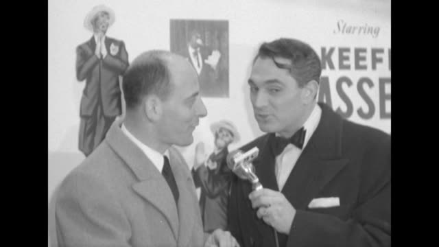 Robert Alda interviews unidentified male celebrity outside the Paramount Theater at the premiere of The Eddie Cantor Story / CU of caricature drawing...