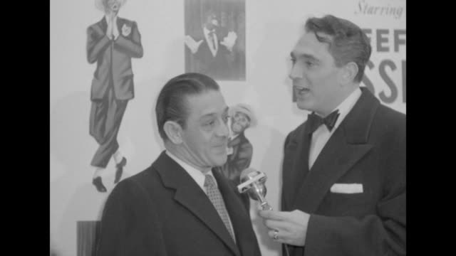 Robert Alda interviews unidentified male celebrity outside the Paramount Theater at the premiere of The Eddie Cantor Story