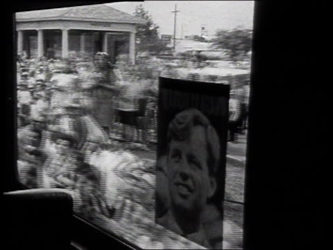 vidéos et rushes de robert f kennedy riding on a train entering station with cheering crowds waiting / united states - 1968