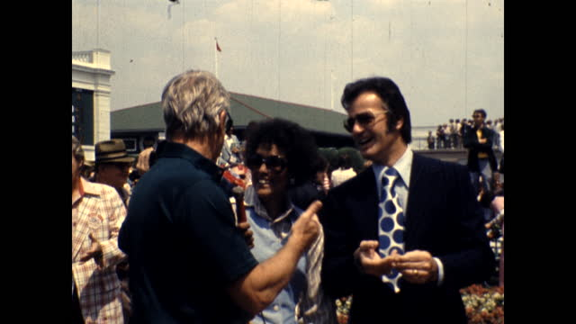 robert goulet and leslie nielsen speak to an african american woman reporter. he shows off the patterned lining of his suit. - robert goulet stock videos & royalty-free footage