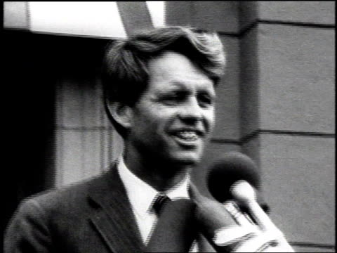 stockvideo's en b-roll-footage met robert kennedy smiling behind microphone / united states - alleen één oudere man