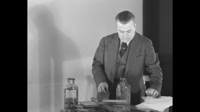 robert l. godby, syracuse, chief, united states secret service, stands at table, holds up bottles containing ink and chemicals, counterfeit money... - bundle stock videos & royalty-free footage