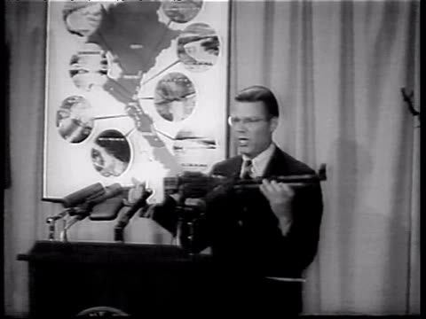 Robert McNamara displaying and holding Red Chinese machine gun and talking at podium then using pointer on map during speech about Vietnam War Robert...