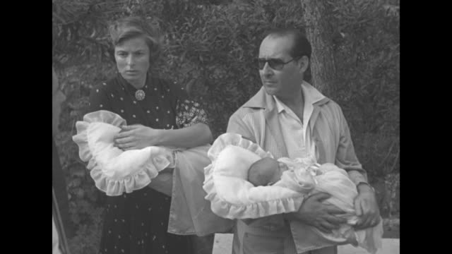 vídeos y material grabado en eventos de stock de ms roberto rossellini walks towards camera carrying infant daughter in gown on a white pillow in garden several reporters follow building in... - paramount building