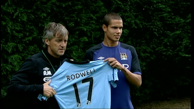 Robin Van Persie signs for Manchester United Jack Rodwell photocall with City Manager Roberto Mancini holding shirt with 'Rodwell' on back Roberto...