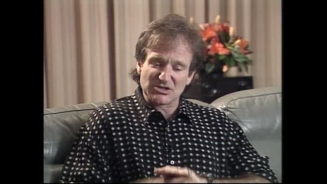vídeos de stock e filmes b-roll de robin williams speaking about america's puritan heritage and automatic weapons in 1996 during interview with host ewart barnsley - robin williams ator