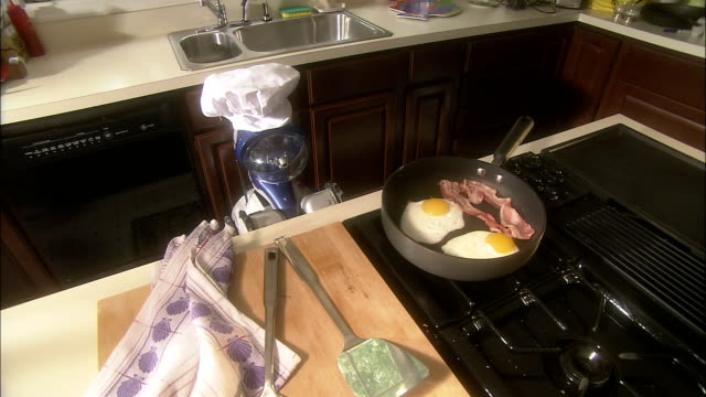 a robot cooks bacon and eggs in a skillet. - protein stock videos & royalty-free footage