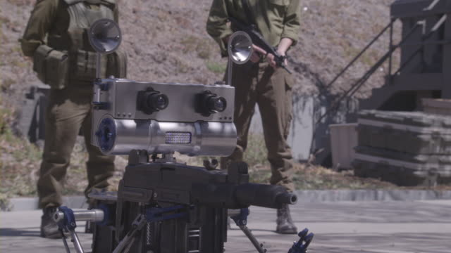 A robot guarded by Israeli soldiers firing an assault rifle.