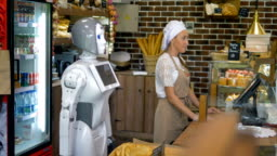 A robot helps a sales girl in a bakery.