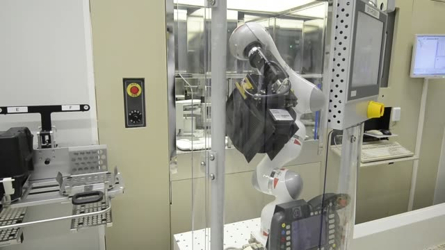 robot moves along conveyor belt and unloads transport box containing semiconductor wafers out of implementation station infineon technologies ag... - regensburg stock videos & royalty-free footage