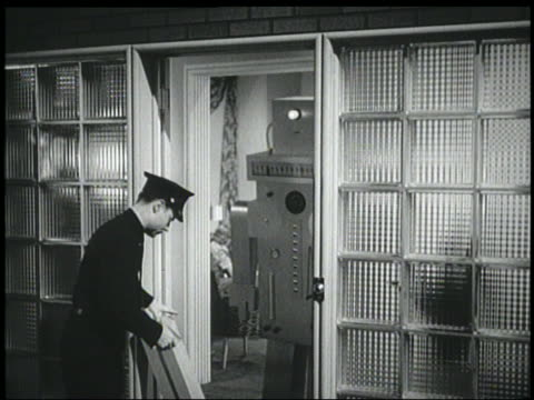 B/W 1940 robot opens door to delivery man who runs away frightened after asking for signature