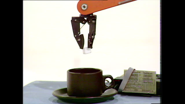 robot picks up sugar cube and drops into cup; 1983 - robot video stock e b–roll
