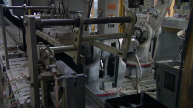 a robot places components into wet-cell battery carcasses on an assembly line. - batteri bildbanksvideor och videomaterial från bakom kulisserna