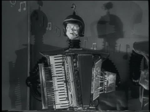vídeos de stock e filmes b-roll de b/w 1958 robot playing accordion - acordeão instrumento