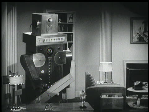 B/W 1940 robot puts box of flowers on table in living room / woman joins him with vase