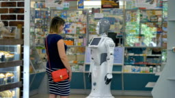 A robot shakes hands with a female customer.