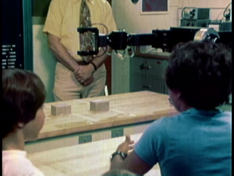 1976 MONTAGE Robot talking in mechanical voice as scientist and children are watching it move and pick up an object / United States