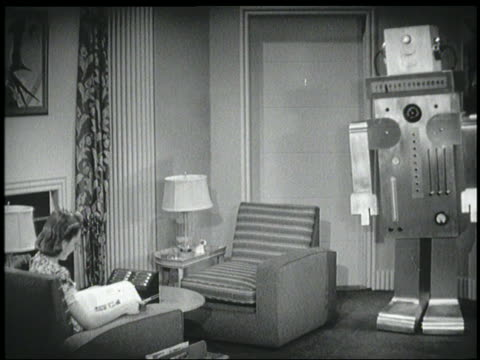 B/W 1940 robot walks while woman reads magazine in chair in living room
