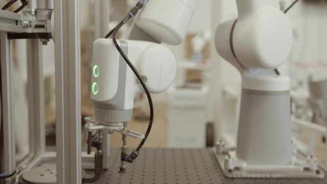 vídeos y material grabado en eventos de stock de robotic arm doing repetitive task - brazo robótico herramientas de fabricación