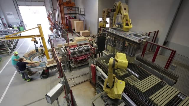 a robotic arm lifts mineral rock wool to be used in porotherm insulated bricks from a conveyor belt on the production line at the wienerberger ag... - traditionally austrian stock videos & royalty-free footage