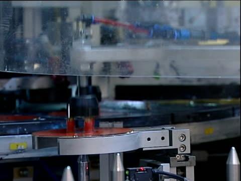 Robotic arm maneuvers compact discs on production line