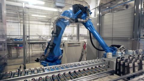 vídeos de stock, filmes e b-roll de a robotic arm packs tubes onto plastic trays - factory