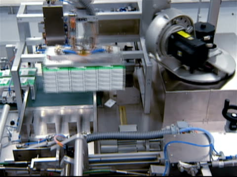 robotic arm placing box of pharmaceuticals on palette / packing box with packaged pharmaceuticals / box being sealed on assembly line / robotic arm picking up box and placing on palette - medical supplies stock videos & royalty-free footage