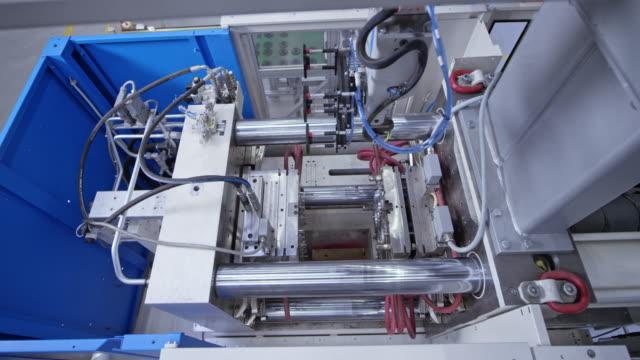 vidéos et rushes de ld bras robotique prenant des produits en plastique hors de la machine de moulage - slovénie
