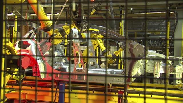 vídeos de stock, filmes e b-roll de robotic arms building a car inside a factory. - indústria automobilística