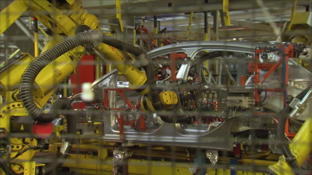 robotic arms building a car inside a factory. - automobile industry video stock e b–roll