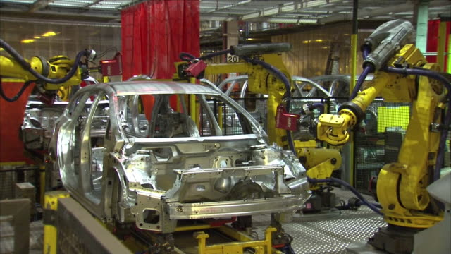 stockvideo's en b-roll-footage met robotic arms building a car inside a factory. - autofabriek