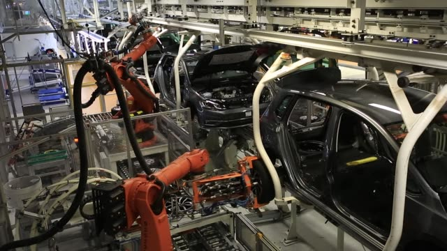 vídeos de stock, filmes e b-roll de robotic arms fit wheels to volkswagen ag automobiles sits on a conveyor belt inside the vw factory in emden germany on friday march 9 photographer... - meio de transporte
