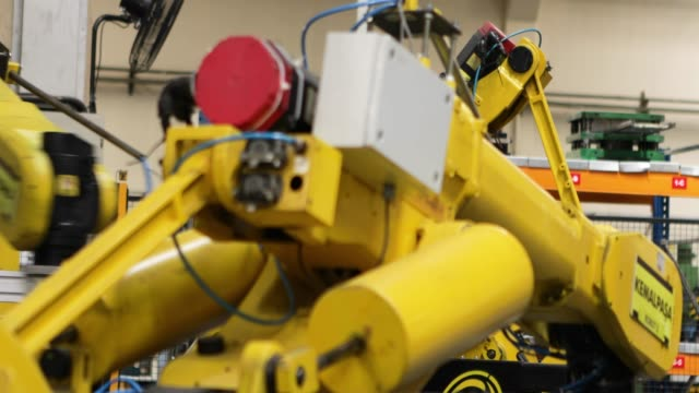vídeos de stock e filmes b-roll de robotic arms in a factory - automatizado