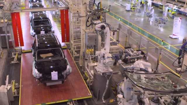 Robotic arms manufactured by ABB Inc work on the front and rear windows of Trumpchi brand vehicles on a production line at the Guangzhou Automobile...