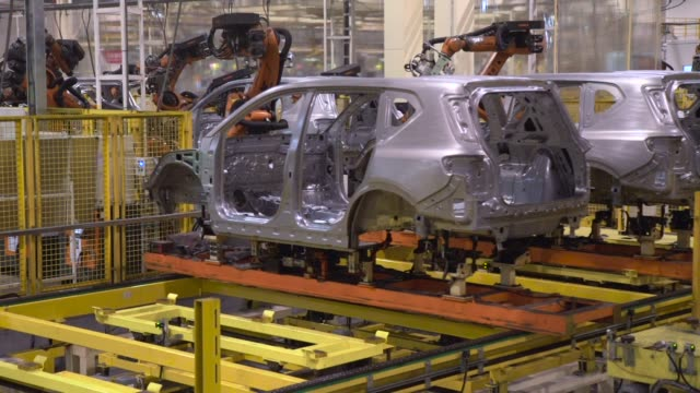 Robotic arms manufactured by Kuka AG work on the chassis of Trumpchi brand vehicles on a production line at the Guangzhou Automobile Group Co Ltd...