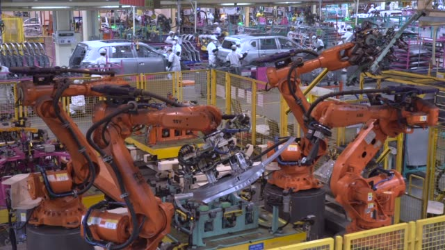 Robotic arms manufactured by Kuka AG work on the door of Trumpchi brand vehicles on a production line at the Guangzhou Automobile Group Co Ltd plant...