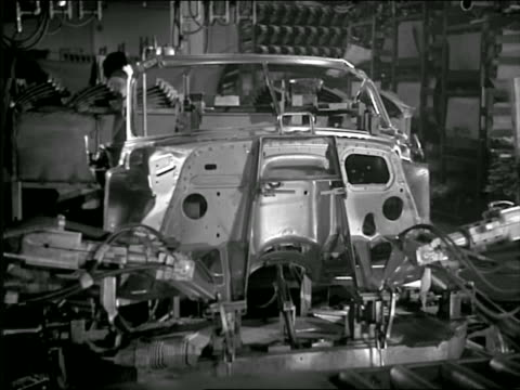B/W 1950 robotic arms + men working on automobile body in factory / sparks flying
