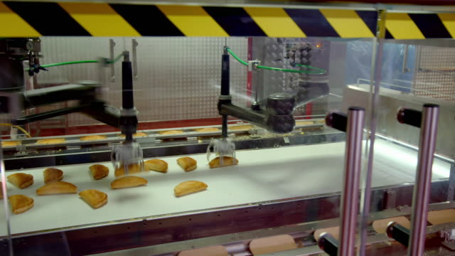 robotic arms move pasties onto paper packaging - manufacturing machinery stock videos & royalty-free footage
